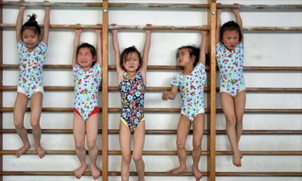 Equipe de ginástica se aquece numa escola de ensino fundamental de Xangai.