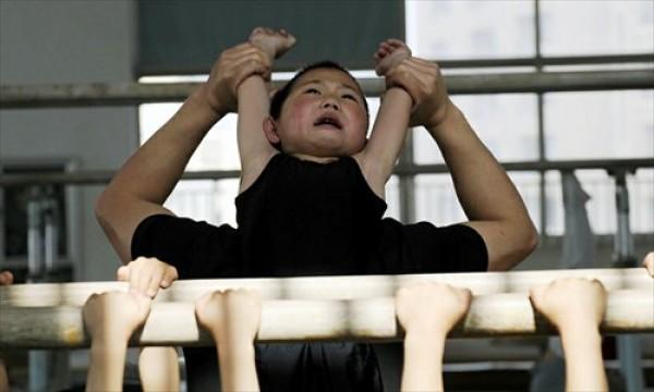 Técnico estira costas de aluno da Escola de Esportes para Crianças em Jiaxing, Província de Zhejiang (leste).